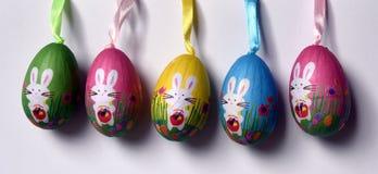 Oeufs de pâques en plastique haletés colorés avec les lapins blancs dans une rangée Photographie stock