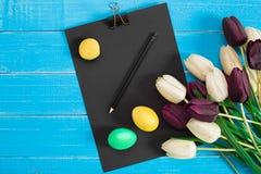 Oeufs de pâques et bouquet colorés des tulipes sur le fond en bois avec l'espace pour un texte Images libres de droits