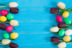 Oeufs de pâques et bouquet colorés des tulipes sur le fond en bois avec l'espace pour un texte Images stock
