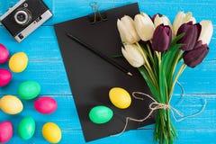 Oeufs de pâques et bouquet colorés des tulipes sur le fond en bois avec l'espace pour un texte Image stock