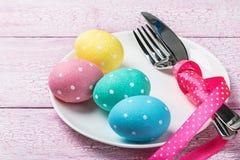 Oeufs de pâques et couverts colorés Photographie stock