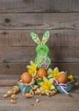 Oeufs de pâques et le lapin de Pâques avec des fleurs des narcisses Photos stock