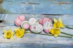 Oeufs de pâques et narcisse roses sur un fond en bois bleu Image libre de droits
