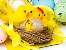 Oeufs de pâques et poulets jaunes sur le fond blanc photographie stock libre de droits