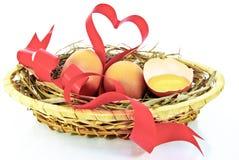 Oeufs de pâques et ruban rouge sous forme de coeur Image stock