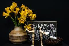 Oeufs de pâques heureux de ressort avec deux mannequins Photographie stock