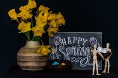 Oeufs de pâques heureux de ressort avec deux mannequins Images stock