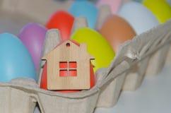 Oeufs de pâques multicolores et jouet en bois de maison Image stock