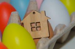 Oeufs de pâques multicolores et jouet en bois de maison Image libre de droits