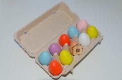 Oeufs de pâques multicolores et jouet en bois de maison Photos stock