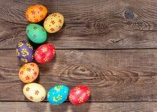 Oeufs de pâques multicolores sur le vieux conseil Image stock