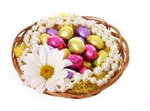 Oeufs de pâques, oeufs de chocolat colorés avec la fleur de camomille et colliers de perle dans le panier Image stock