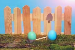 Oeufs de pâques peints à la barrière en bois sur la mousse verte Photographie stock