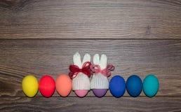 Oeufs de pâques peints à la main avec les chapeaux tricotés de lapin au-dessus du fond en bois avec l'espace de copie Joyeuses Pâ photographie stock