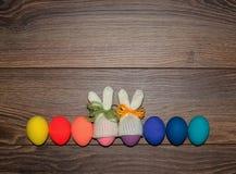 Oeufs de pâques peints à la main avec les chapeaux tricotés de lapin au-dessus du fond en bois avec l'espace de copie Joyeuses Pâ images stock