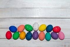Oeufs de pâques peints à la main sur le fond en bois Joyeuses Pâques image libre de droits