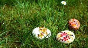 Oeufs de pâques peints colorés sur une herbe verte Images stock