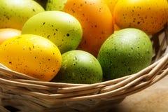 Oeufs de pâques peints dans orange, jaune et vert dans un panier, clo Photos stock