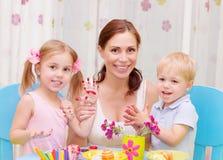 Oeufs de pâques peints par famille heureuse Photographie stock libre de droits