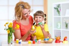 Oeufs de pâques peints par fille de mère et d'enfant Photographie stock