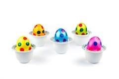 Oeufs de pâques peints se tenant dans des coquetiers de porcelaine sur le blanc Images stock
