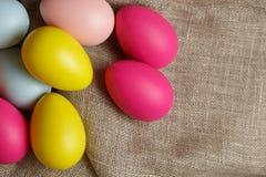 Oeufs de pâques peints sur la toile à sac, composition de fête rustique photos libres de droits