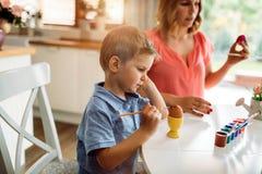 Oeufs de pâques de peinture de mère et de fils photographie stock