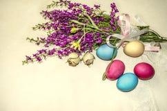 Oeufs de pâques près du bouquet des fleurs sauvages pourpres enveloppées dans la bande de dentelle Photographie stock libre de droits