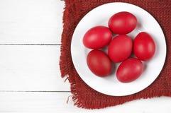 Oeufs de pâques rouges dans le plat images stock