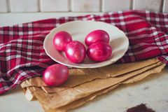 Oeufs de pâques rouges lumineux du plat sur la serviette rouge vérifiée et le papier brun de métier sur la table Photo stock