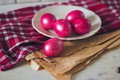 Oeufs de pâques rouges lumineux du plat sur la serviette rouge vérifiée et le papier brun de métier sur la table Images libres de droits