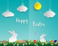 Oeufs de pâques sur l'herbe verte avec le lapin blanc, la petite marguerite, le papillon, le nuage et le soleil sur le fond bleu  Image libre de droits