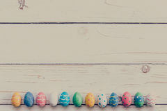 Oeufs de pâques sur le fond en bois Oeufs et main de pâques colorés Photographie stock