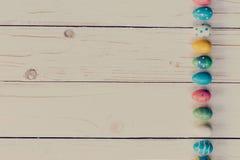 Oeufs de pâques sur le fond en bois Oeufs et main de pâques colorés Images stock