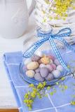 Oeufs de pâques tachetés colorés de chocolat dans cloche en verre en cristal avec le ruban sur la serviette bleue sur la table bl Photos libres de droits
