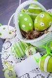 Oeufs de pâques verts colorés en paille Photo stock