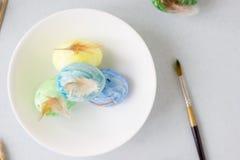 Oeufs de pâques verts, jaunes et bleus sur le tir de cuvette, lumineux et bien aéré en céramique Photos libres de droits