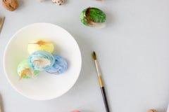 Oeufs de pâques verts, jaunes et bleus sur le tir de cuvette, lumineux et bien aéré en céramique Photographie stock libre de droits