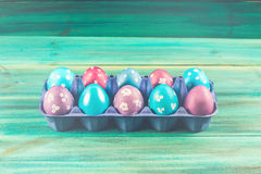 Oeufs de pâques violets et bleus dans des plateaux de carton Fond en bois bleu Joyeuses Pâques photographie stock