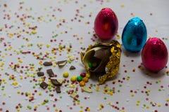 Oeufs de p?ques d'or cass?s de chocolat avec des chocolats color?s ? l'int?rieur sur le fond blanc avec les confettis brouill?s c photographie stock libre de droits