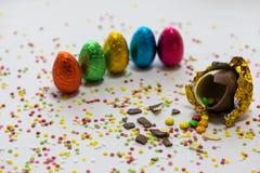 Oeufs de p?ques d'or cass?s de chocolat avec des chocolats color?s ? l'int?rieur sur le fond blanc avec les confettis brouill?s c images libres de droits