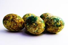 Oeufs de p?ques verts jaunes faits main peints marbr?s au-dessus du fond blanc photographie stock libre de droits