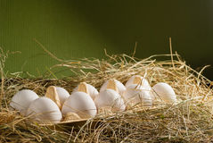 Oeufs de poulet dans la paille Fond rustique en bois Images stock