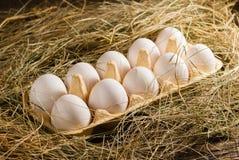 Oeufs de poulet dans la paille Fond rustique en bois Photographie stock libre de droits