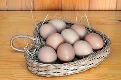 Oeufs de poulet dans un panier en osier en forme de coeur Photographie stock libre de droits