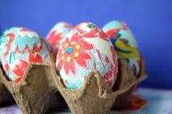 Oeufs de pâques décorés dans un carton Photo stock
