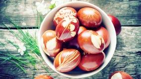 Oeufs de pâques sur le Tableau en bois décoré des feuilles fraîches naturelles Photographie stock
