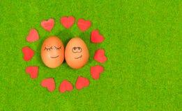 Oeufs drôles dans l'amour sur une herbe verte Image stock