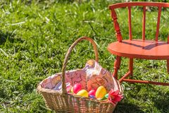 Oeufs en plastique dans le panier de Pâques s'étendant dans l'herbe verte grande avec la chaise orange Image libre de droits