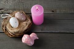 Oeufs et bougie rose d'arome sur le vieux fond en bois Images stock